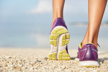 Crropped Shot Of Unrecognizable Female In Purple Sneakers Stands On Shell Beach, Wears Sport Shoes, Has Morning Workout Or Jogging Outdoor, Being In Movement. Sport And Healthy Lifestyle Concept