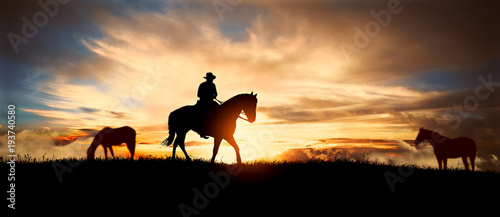 Poster Brun profond A silhouette of a cowboy and horse at sunset