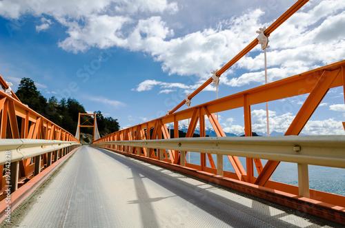 red-suspension-bridge-over-the-water-runoff-of-general-carrera-lake-near-lake-bertrand-puerto-tranquilo-chile-chico-aysen-chile