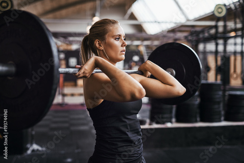 Fit young woman lifting heavy weights alone in a gym Tapéta, Fotótapéta