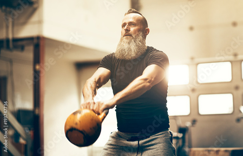 Fotografiet  Fit mature man swinging a dumbbell at the gym