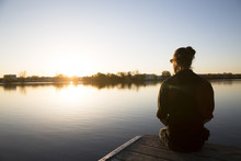 Man Sits On A Dock Looking Over Still Water