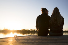 Man And Women Sit Closely Together On A Dock On A Lake