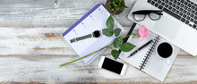 Overhead View Of Office Desktop With Lovely Pink Rose On White Rustic Wooden Desktop