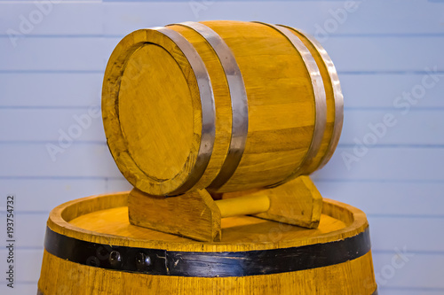 Small And Large Beer Barrels In The Studio On A Blue Background