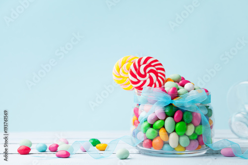 Confiserie Jar staffed sweet colorful candy against turquoise background. Gifts for Birthday party.