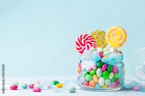 Poster Confiserie Sweet colorful candy in jar decorated with bow ribbon against blue background. Gifts for Birthday party.