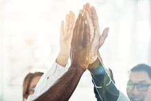 Diverse Businesspeople High Fiving Together In An Office