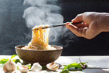Hand Uses Chopsticks To Pickup Tasty Noodles With Steam And Smoke In Bowl On Wooden Background, Selective Focus
