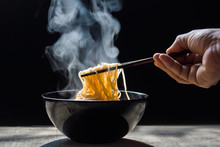 Hand Uses Chopsticks To Pickup Tasty Noodles With Steam And Smoke In Bowl On Wooden Background, Selective Focus.  Top View, Asian Meal On A Table, Junk Food Concept