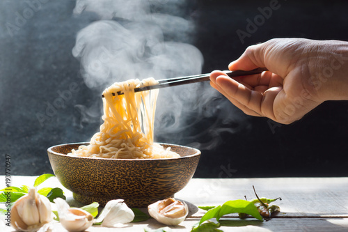Fotobehang Rook Hand uses chopsticks to pickup tasty noodles with steam and smoke in bowl on wooden background, selective focus