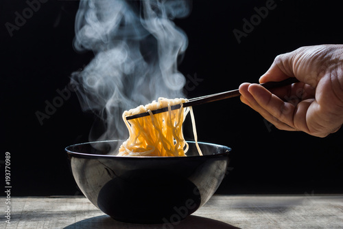Fotomural  Hand uses chopsticks to pickup tasty noodles with steam and smoke in bowl on wooden background, selective focus