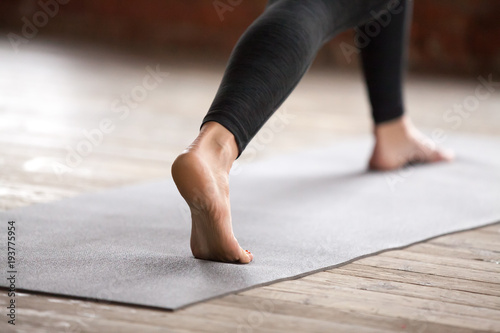 Poster Ecole de Yoga Young sporty woman practicing yoga, doing Warrior one exercise, Virabhadrasana 1 pose, working out, wearing black sportswear, indoor, yoga studio close up. Healthy lifestyle concept