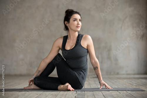 Poster Ecole de Yoga Young sporty woman practicing yoga, doing Ardha Matsyendrasana exercise, Half lord of the fishes pose, working out, wearing sportswear, black pants and top, indoor full length, gray wall, yoga studio