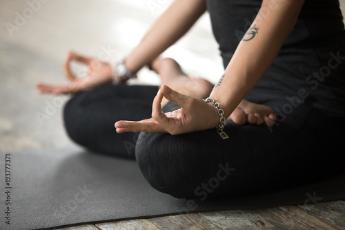 Young sporty woman practicing yoga, doing Padmasana exercise, Lotus pose with mudra gesture, working out, wearing sportswear, black pants and top, indoor close up view, yoga studio