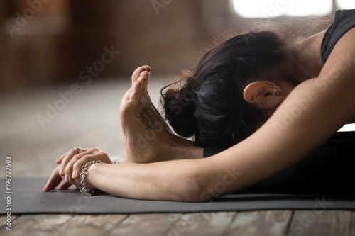 Recess Fitting Yoga school Young sporty woman practicing yoga, doing paschimottanasana exercise, Seated forward bend pose, working out, wearing black sportswear, indoor close up view, yoga studio