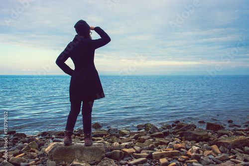 woman looking out at the sea in winter season, young lady with black coat and wooden hat seeking the horizon