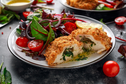 Poster Kiev Breaded Chicken Kiev breast stuffed with butter, garlic and herbs served with vegetables in a plate.