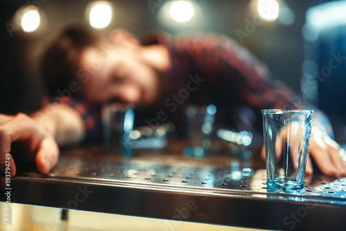 Fotografering Drunk man sleeps at bar counter, alcohol addiction