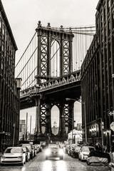 Panel Szklany Podświetlane Do biura Manhattan Bridgeas seen from Washington street in Brooklyn, New York City, USA. Motion blured jogger running in foreground. Black and white image.