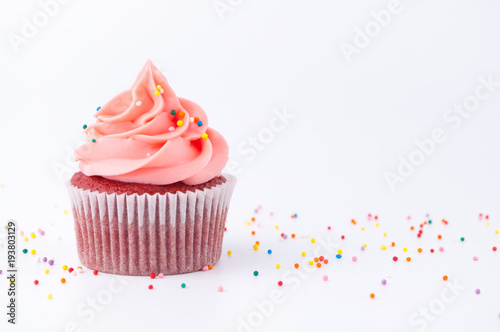 Платно Cupcake red velvet with blue and pink whipped cream decorated with colorful sprinkles on white background
