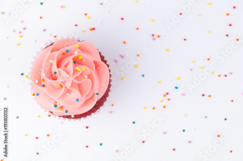 Photo  Cupcake red velvet with blue and pink whipped cream decorated with colorful sprinkles on white background
