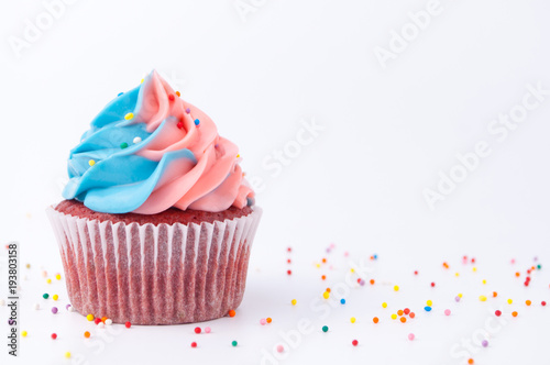 Cupcake red velvet with blue and pink whipped cream decorated with colorful sprinkles on white background Wallpaper Mural