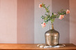 Pink flowers in chrome vase on fur with striped background pink glow