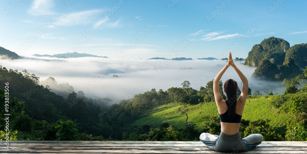 Fototapeta Young woman practicing yoga in the nature