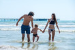 Mom, dad and son splashing in the sea on warm sunny day. Holding hands together