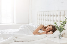 Horizontal Shot Of Relaxed Carefree Female Under White Bedclothes In Bed At Bedroom, Sees Pleasant Dreams, Keeps Eyes Closed, Enjoys Good Rest At Home And Calm Atmosphere. People And Rest Concept