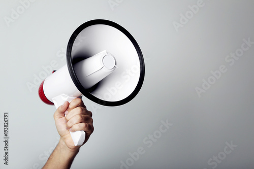 Fényképezés  Female hand holding megaphone on grey background