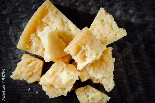 pieces of Parmesan cheese on a dark wooden background.