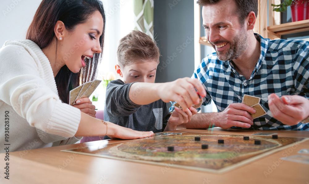 Fototapeta Happy family playing board game at home