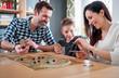 Leinwandbild Motiv Happy family playing board game at home
