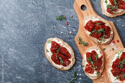 Bread slices with cream cheese and sun dried tomatoes on wooden table top view. Delicious snack and appetizer.