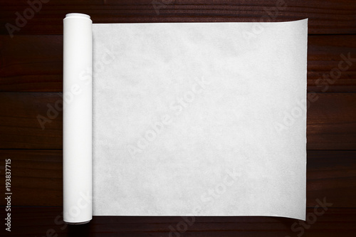 Fotografie, Obraz  Eine Rolle Backpapier ausgerollt auf dunklem Holz, fotografiert mit natürlichem