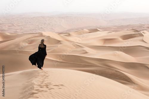Fotografía Young beautiful Caucasian woman posing in a traditional Emirati dress - abaya in Empty Quarter desert landscape