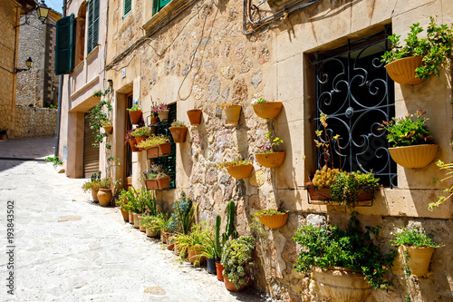 Wall Murals Narrow alley Beautiful street in Valldemossa with traditional flower decoration, famous old mediterranean village of Majorca. Balearic island Mallorca, Spain