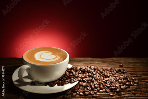 Wall Murals Cafe Cup of coffee latte and coffee beans on reddish brown background