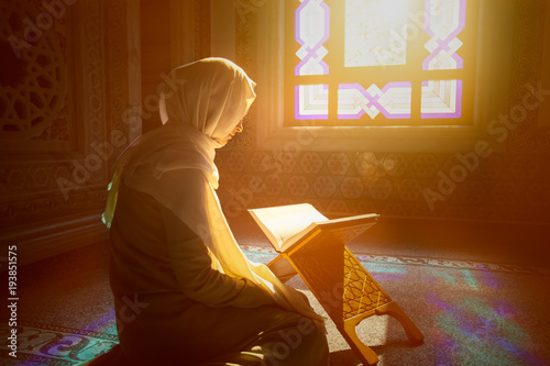 Fényképezés Young muslim woman reading Quran in the mosque and sunlight falling from the win