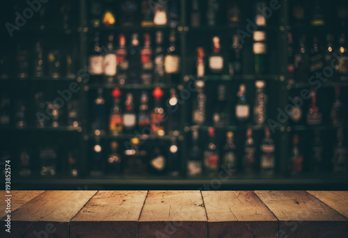 Garden Poster Bar Empty the top of wooden table with blurred counter bar and bottles Background