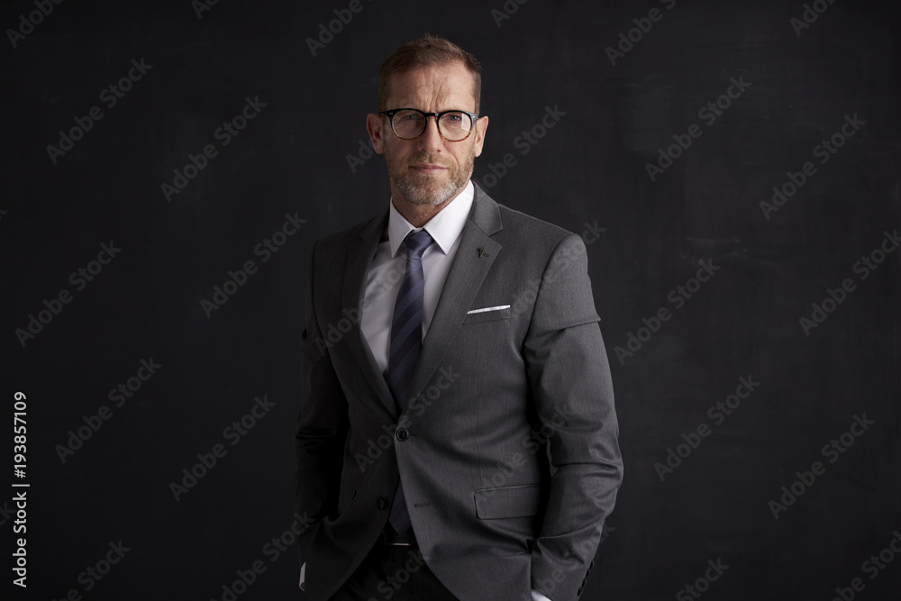 Fototapeta Executive senior businessman portrait. Middle aged financial director business man wearing suit and looking at camera while standing at dark background.