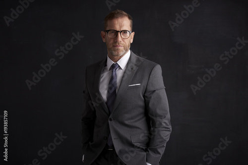 Executive senior businessman portrait. Middle aged financial director business man wearing suit and looking at camera while standing at dark background.