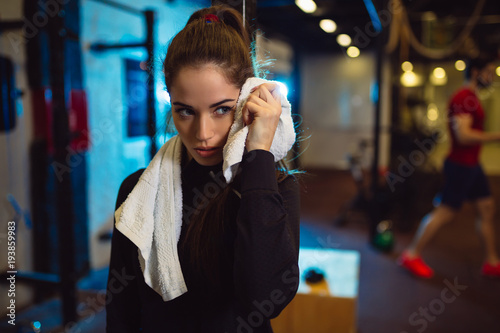 Fotografiet  Tired girl wiping sweat with towel in gym.
