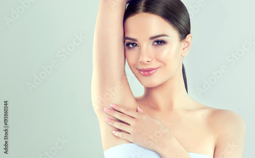 Photo Young woman holding her arms up and showing underarms, armpit smooth clear skin