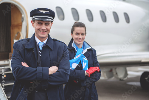 Fototapeta  Portrait of cheerful pilot and happy air-hostess looking at camera while locating opposite airplane