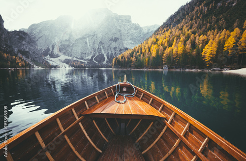 Photo Stands Lake Wooden rowing boat on a lake in the Dolomites in fall