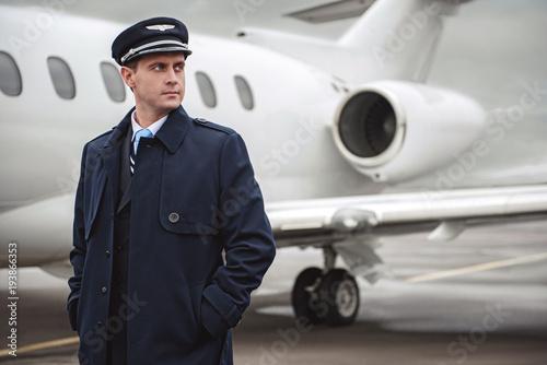 Fototapeta Portrait of serene young pilot putting hands in pocket
