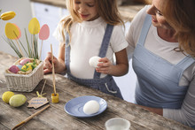 Happy Little Child Sopping The Brush Into Yellow Paint While Holding Egg In Other Hand. Mom Is Looking At Her With Joy
